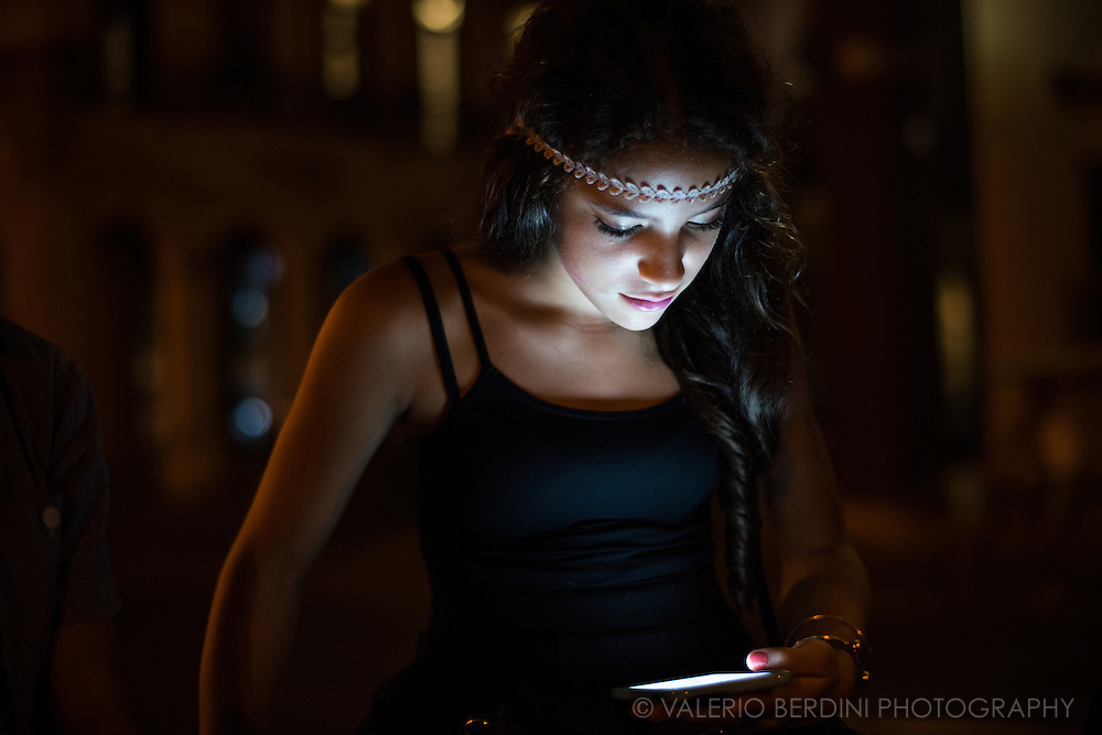 A young girl lit up by her smartphone screen on a bench of Paseo del Prado in Havana, Cuba, on the evening of 27 of December 2015. Since the arrive of wi-fi hotspots, the young Cuban generation is captured and absorbed by the discovery of the online world. This girl was aware of the photographer, but she continued using the smartphone. This photo was not staged.<br />