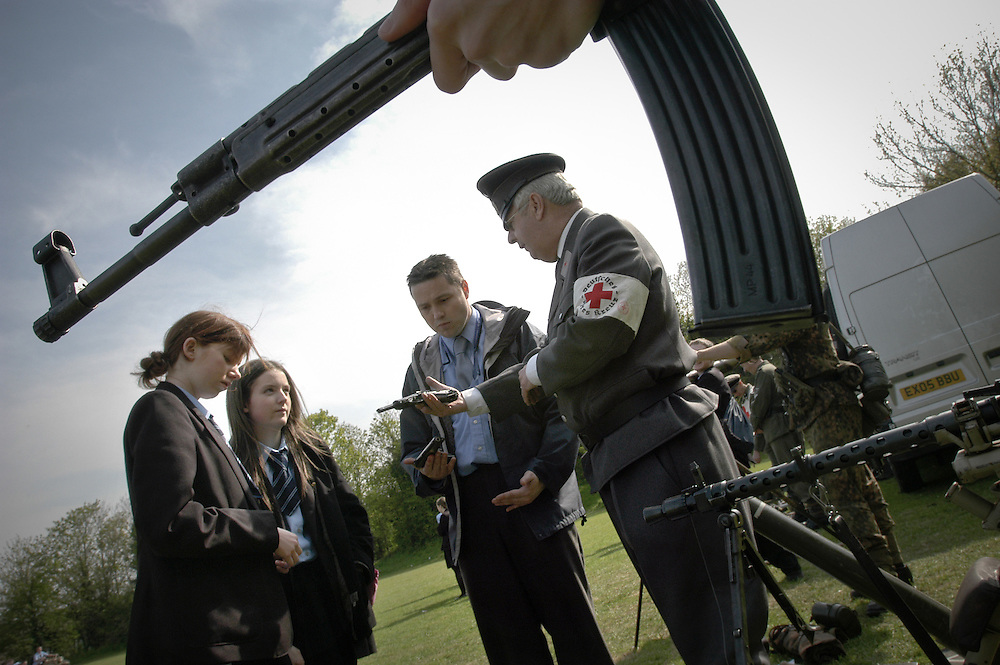 Children from St John's Catholic Comprehensive School in Gravesend play with replica guns with members of Living History groups dressed as German and American WWII soldiers.