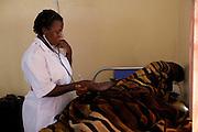 Sister Mampewo Sarah Senkungi checks a patients blood pressure at Kasangati Health Centre in Uganda.