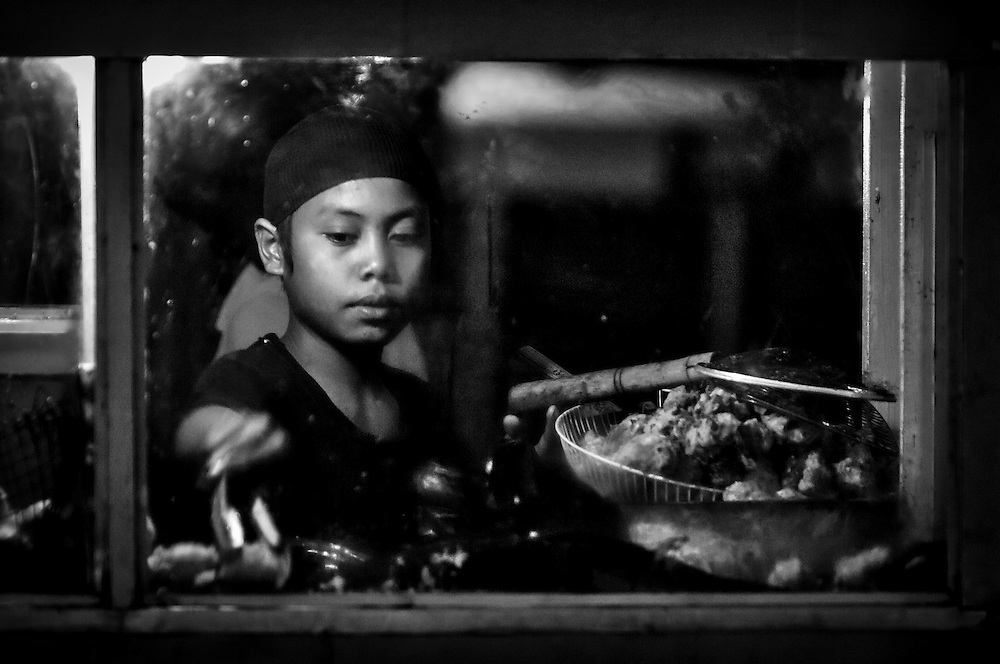 "Portrait of a boy frying chicken in a ""kaki lima"" for sale in a local market in Indonesia. The image is shot at night through the greasy glass of the food cart to emphasise the lack of hygiene in these rural communities."