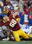 Washington Redskins tackle Tom Compton (68) yells out in pain as a player rolls up on his legs from behind during the NFL week 17 regular season football game against the Dallas Cowboys on Sunday, Dec. 28, 2014 in Landover, Md. The Cowboys won the game 44-17. ©Paul Anthony Spinelli