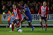 AFC Wimbledon defender Paul Kalambayi (30) battles for possession with Lincoln City defender Jason Shackell (5) during the EFL Sky Bet League 1 match between AFC Wimbledon and Lincoln City at the Cherry Red Records Stadium, Kingston, England on 2 November 2019.