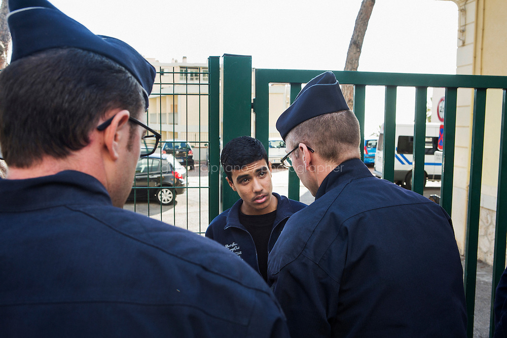 MENTON, FRANCE - 20 NOVEMBER 2014: An Afghan refugee is questioned by the French police after being caught on the train that goes from Ventimiglia to Nice, taken by migrants that want to cross the border from Italy to France, in Menton, France, on November 20th 2014.<br /> <br /> The Ventimiglia-Menton border is the border between Italy and France crossed by migrants who decide to continue their journey up north towards countries such as Germany, Sweden, The Netherlands and the UK where the process to receive the refugee status or humanitarian protection is smoother and faster. in Ventimiglia, Italy, on November 17th 2014.