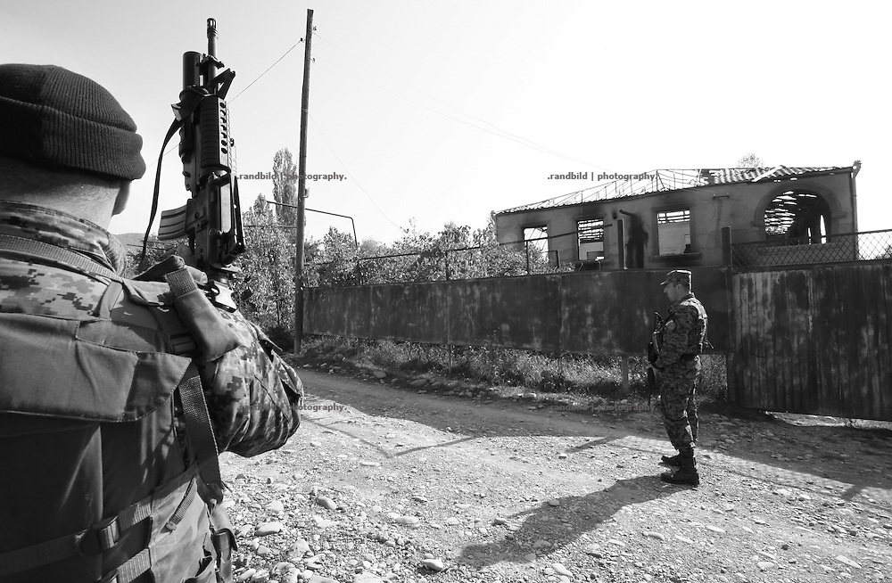 Georgian policemen patroling an area at the frontline in Mereti, after witnesses have seen ossetian fighters at the scene. Mereti is located in the so called bufferzone between Gori and Tskhinvali, few days after the withdrawal of the russian forces from the area. The bufferzone was etablished after a short war in August 2008 as the georgian army assulted South Ossetia to overthrow the local separatist government.