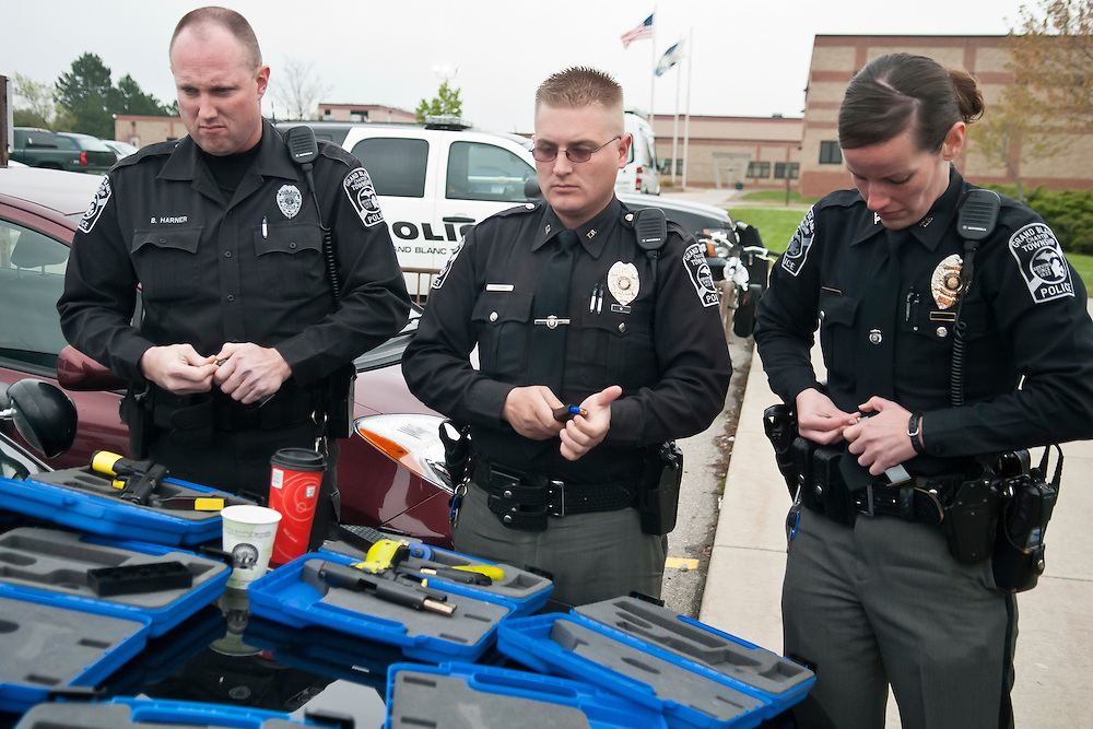 Lathan Goumas | MLive.com..April 26, 2012 - Members of the Grand Blanc Township Police load guns with blank ammunition prior to participating in a live school shooter drill at Grand Blanc High School in Grand Blanc on Thursday. The emergency drill simulated school shooters entering both campuses of Grand Blanc High School and was used as a training exercise for local and state law enforcement officers as well as school faculty and staff.