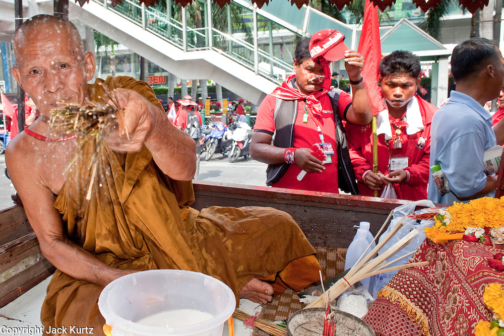 "Apr 4, 2010 - BANGKOK, THAILAND: A Buddhist monk blesses Red Shirts with holy water in Ratchaprasong intersection during the Red Shirts' blockade of the intersection Sunday, Apr 4. Thousands of members of the United Front of Democracy Against Dictatorship (UDD), also known as the ""Red Shirts"" and their supporters moved their anti government protests into central Bangkok Apr. 4 when they occupied Ratchaprasong intersection, the site of Bangkok's fanciest shopping malls and several 5 star hotels. The Red Shirts are demanding the resignation of current Thai Prime Minister Abhisit Vejjajiva and his government. The protest is a continuation of protests the Red Shirts have been holding across Thailand. They support former Prime Minister Thaksin Shinawatra, who was deposed in a coup in 2006 and went into exile rather than go to prison after being convicted on corruption charges. Thaksin is still enormously popular in rural Thailand. This move, away from their traditional protest site in the old part of Bangkok, has gridlocked the center of the city and closed hundreds of stores and restaurants and several religious shrines. There has not been any violence, but the government had demanded that the Red Shirts return to the old part of the city.   PHOTO BY JACK KURTZ"