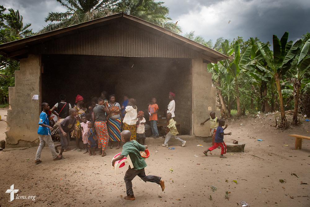 As a thunderstorm blows in, children quickly carry chairs and other items to shelter as a small crowd of patients awaiting prescriptions huddle under the awning during the fifth day of the LCMS Mercy Medical Team on Friday, May 11, 2018, in the Yardu village outside Koidu, Sierra Leone, West Africa. LCMS Communications/Erik M. Lunsford