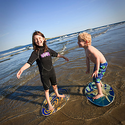 A brother and sister skim boarding at Popham Beach State Park in Phippsburg, Maine.