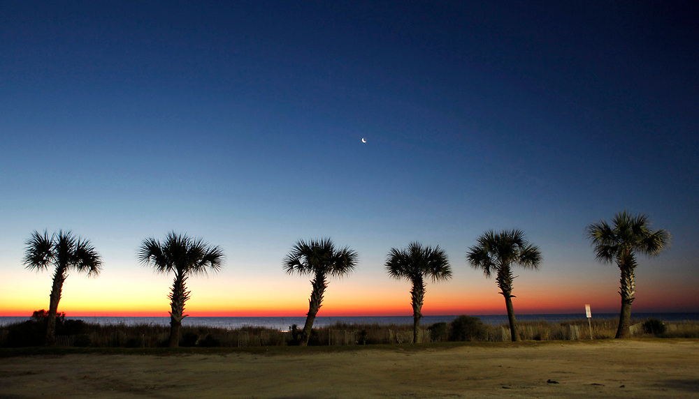 A crescent moon rises over the Atlantic Ocean ahead of the January sunrise.