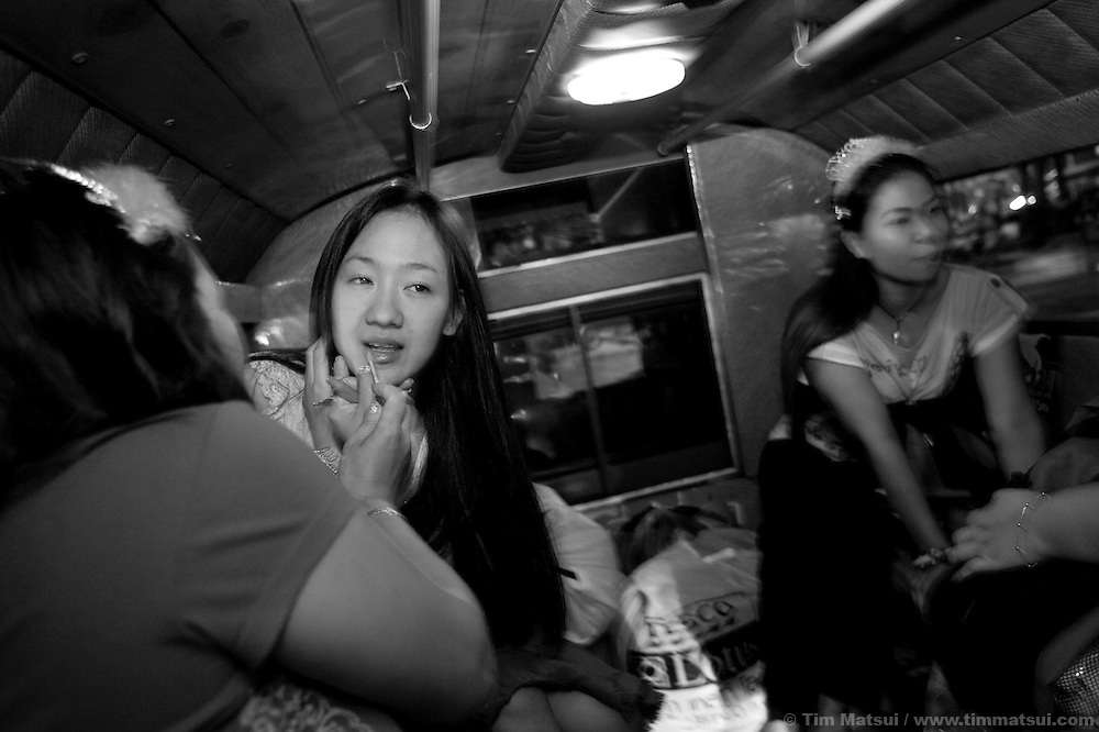 """Women in a Song Tau taxi preparing to go out on Valentine's Day to distribute Empower-branded condoms to sex workers while in Chiang Mai, Thailand, which serves as a drop-in center offering computer and informal English training, health education, counseling and other support to sex workers. Founded in 1985 the organization has five centers from Phuket to Mai Sai and advocates for recognition, equality, and basic human rights for sex workers in Thai society where sex work is common, visible, and yet illegal..>>.Empower Chiang Mai opened the """"Can-Do"""" bar which offers fair working conditions to sex workers by complying with all Thai Labor Laws and the recommended occupational health and safety standards..>>.Empower, which works with women over 18 years-old and is a vocal opponent of human trafficking, sexual or labor exploitation of any person,  is also campaigning to change the methods of anti-human trafficking groups. Empower states """"the focus on trafficking in persons has meant many groups with little or no experience on the issues of migration, labor, sex work or women's rights have been created to take advantage of the large sums of money available to support anti-trafficking activities."""".>>.Recommendations by sex workers, many who were Burmese, some who had been trafficked, and all who acknowledged enlisting an agent to migrate illegally into Thailand, stated among other things that """"The primary goal of prosecuting traffickers must be altered to a primary goal of assisting trafficked women and children...if trafficked women and children...are continually rescued and assisted, the use of trafficked women and children will become unprofitable...we are willing to work our illegal status leaves us with no recourse against exploitation by agents or employers...Anti-trafficking groups must work toward improving the human rights situation...Anti-trafficking dialogue and groups have yet to consider us as anti-trafficking workers and human rights defenders...The latest s"""
