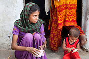 Sadma Khan (in purple), 19, makes lunch as her 18 month old son plays by her side in the shared compound of her mother's (in orange) extended family's house in a slum area of Tonk, Rajasthan, India, on 19th June 2012. She was married at 17 years old to Waseem Khan, also underaged at the time of their wedding. The couple have an 18 month old baby and Sadma is now 3 months pregnant with her 2nd child and plans to use contraceptives after this pregnancy. She lives with her mother since Waseem works in another district and she can't take care of her children on her own. Photo by Suzanne Lee for Save The Children UK