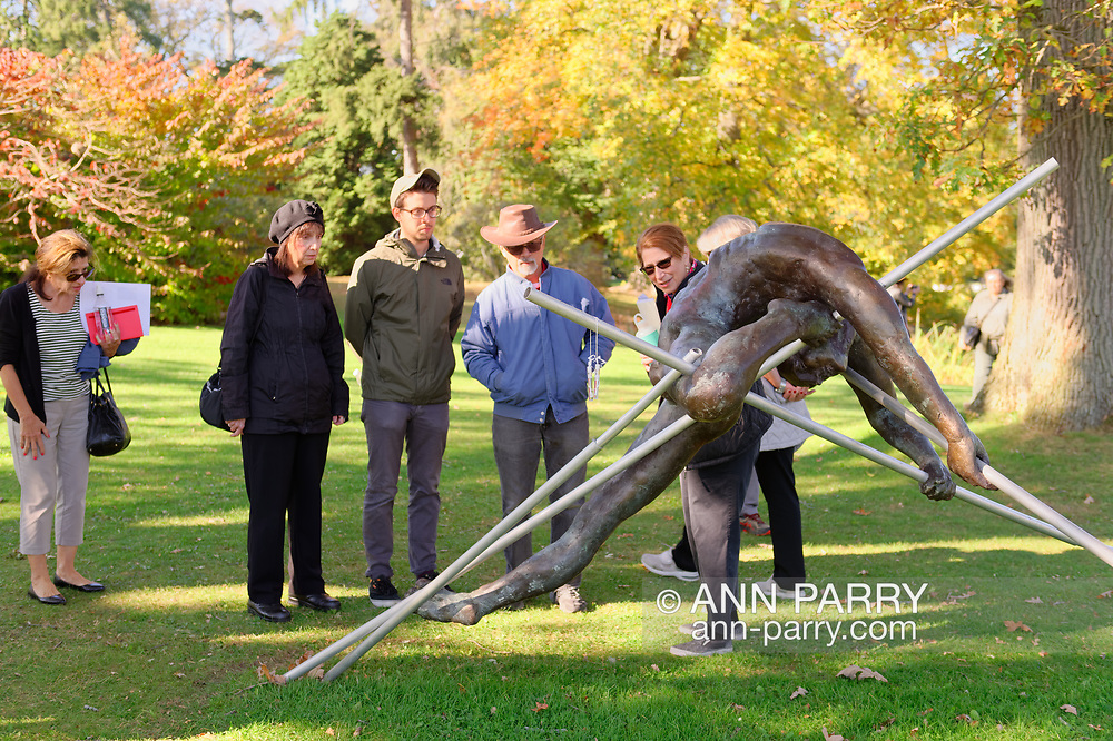 Old Westbury, New York, U.S. October 19, 2019. At right, docent LUCY JAFFE leads tour during Closing Reception for Jerzy Kędziora (Jotka) Balance in Nature outdoor sculptures exhibit, held at Old Westbury Gardens.