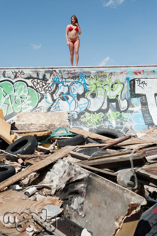 Young woman in bikini standing on graffiti wall with garbage in foreground