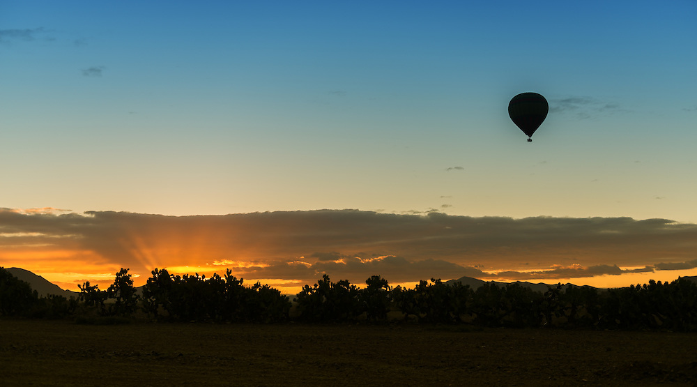 Hot-air balloon silhouette at sunrise.
