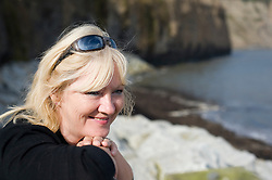 Attractive blonde older Woman looks out to sea over Robin Hoods Bay north Yorkshire