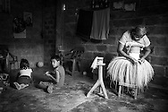 "2015/03/13 - Pile, Ecuador: Mariana Rivera, 73, weaves a ""Montecristi hat"" in her house early in the morning, while her grandchildren play. She started to weave hats at the age of 10. Nowadays she doesn't weave the finest hats as before because her eyes are tired and old as she says. So, Mariana uses thicker straw to weave a hat, which brings the price down. She sells them at around US$200, but sometimes even less if she is really desperate for money.  UNESCO declared the ""Montecristi hat"" in 2012 as Intangible Cultural Heritage of Humanity."