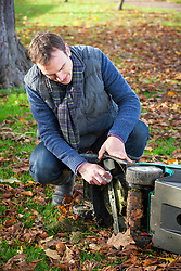 Cleaning lawnmower blades with a rag in the autumn