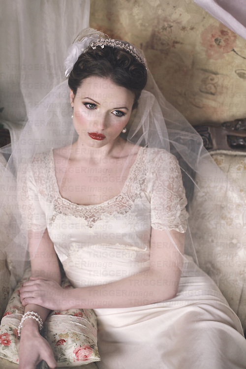 A gorgeous vintage caucasian bride in her early 20s sits in a fancy wedding room, looking serious