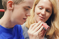 Carer with teenage boy with autism looking at toy truck,