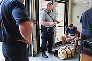 EMS officer/firefighter paramedic Chris Hickey, facing center, talks with two walk-in addicts including John Mandravelis, 27, homeless, sitting, at the Main Fire Station in Manchester, NH Wednesday, Aug. 10, 2016.  This is John Mandravelis's third time seeking help at the station for help since June, he was later turned away from the recovery center he was taken to.<br /> To help combat Manchester New Hampshire's huge drug problem, anyone can walk into the main fire station seeking help, they'll get connected with a drug counselor and services. Something like 230 people have shown up in the first couple months and it's quickly spawning copy-cat programs.  <br />    (Cheryl Senter for The Wall Street Journal)