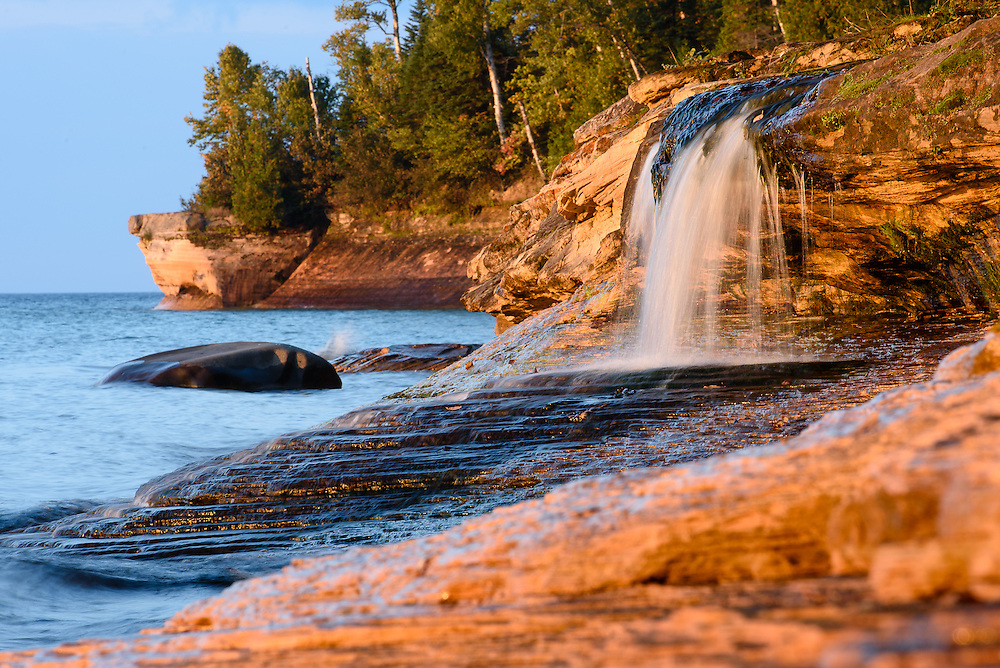 PICTURED ROCKS NATIONAL LAKESHORE - October 2016: Going to Elliot Falls, aka Miners Beach Falls, at sunset is popular among park visitors and photographers in Pictured Rocks National Lakeshore. But not just for the sunset across the rocks but for how the setting sun transforms the color of the rocks into a golden-brown tone.  <br />
