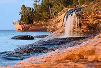 PICTURED ROCKS NATIONAL LAKESHORE - October 2016: Going to Elliot Falls, aka Miners Beach Falls, at sunset is popular among park visitors and photographers in Pictured Rocks National Lakeshore. But not just for the sunset across the rocks but for how the setting sun transforms the color of the rocks into a golden-brown tone.  <br /> Photographer Bryan Mitchell was this years Artist in Residence at Pictured Rocks National Lakeshore in the Upper Peninsula of Michigan from Oct. 1-17, 2016 near Munising, Michigan. (Photo by Bryan Mitchell)