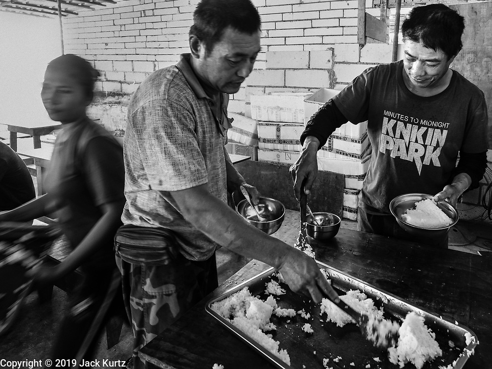 """15 FEBRUARY 2019 - SIHANOUKVILLE, CAMBODIA: Chinese construction workers get lunch at the dining hall in the housing complex at which they live. There are about 80 Chinese casinos and resort hotels open in Sihanoukville and dozens more under construction. The casinos are changing the city, once a sleepy port on Southeast Asia's """"backpacker trail"""" into a booming city. The change is coming with a cost though. Many Cambodian residents of Sihanoukville  have lost their homes to make way for the casinos and the jobs are going to Chinese workers, brought in to build casinos and work in the casinos.     PHOTO BY JACK KURTZ"""