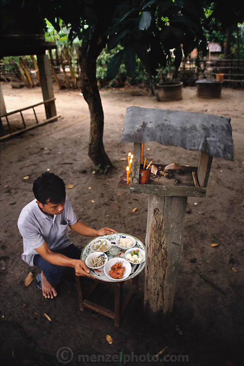 Boontham Khuenkaew places an offering of cucumbers, red pork, bamboo shoot stew, shrimp-paste, and rice before the spirit house in his yard. Spirit houses are the abodes of the many spirits that Thais regard as integral parts of the land. Because the spirits have the power to cause trouble, Boontham periodically placates them by lighting candles and placing a good meal there. He puts a little rice on the ground, and adorns the house with flowers. Published in Material World page 85. The Khuenkaew family lives in a wooden 728-square-foot house on stilts, surrounded by rice fields in the Ban Muang Wa village, outside the northern town of Chiang Mai, in Thailand.