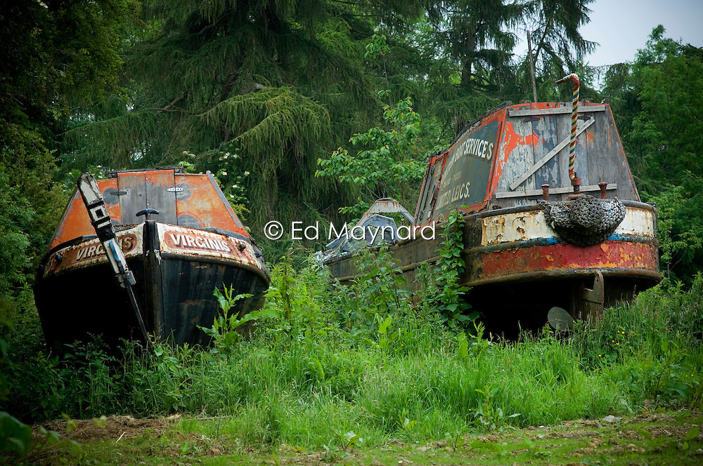 Old canal boats on dry land by the roadside near Foxton Locks on the Grand Union Canal, Market Harborough, Leicestershire, England, UK.