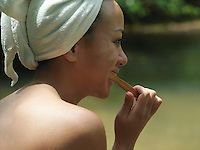 Young woman brushing teeth with towel wrapped on head side view