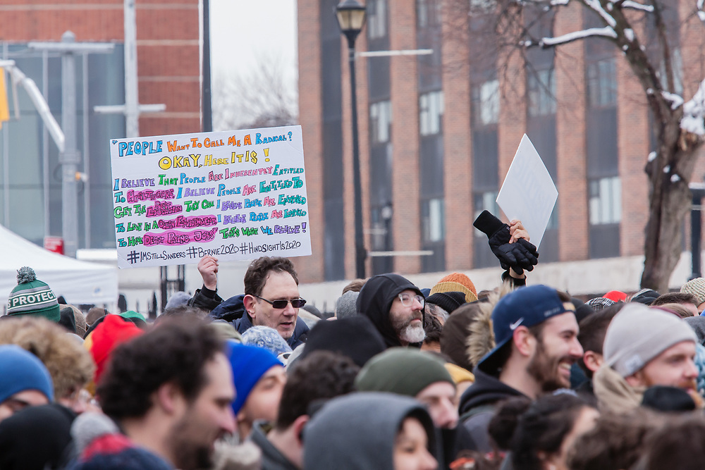 Brooklyn, NY - 2 March 2019. A man holds a lengthy sign describing political radicalism at Bernie Sanders' first rally for the 2020 presidential primary at Brooklyn College.