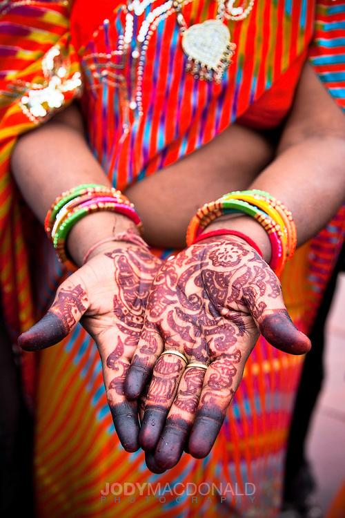 Woman in India with henna tatoos on hands wearing red shawl