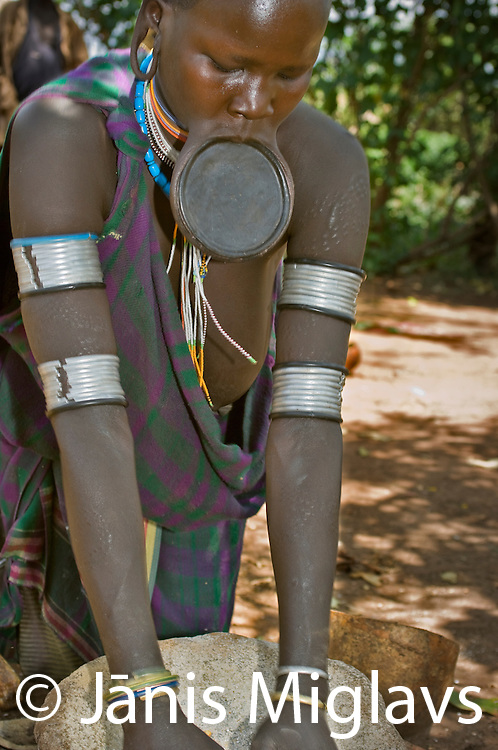 Suri woman with lip plate working and ochre butter on her face grinding grain on a stone in Regia region, Bargoba village, Omo, Ethiopia.