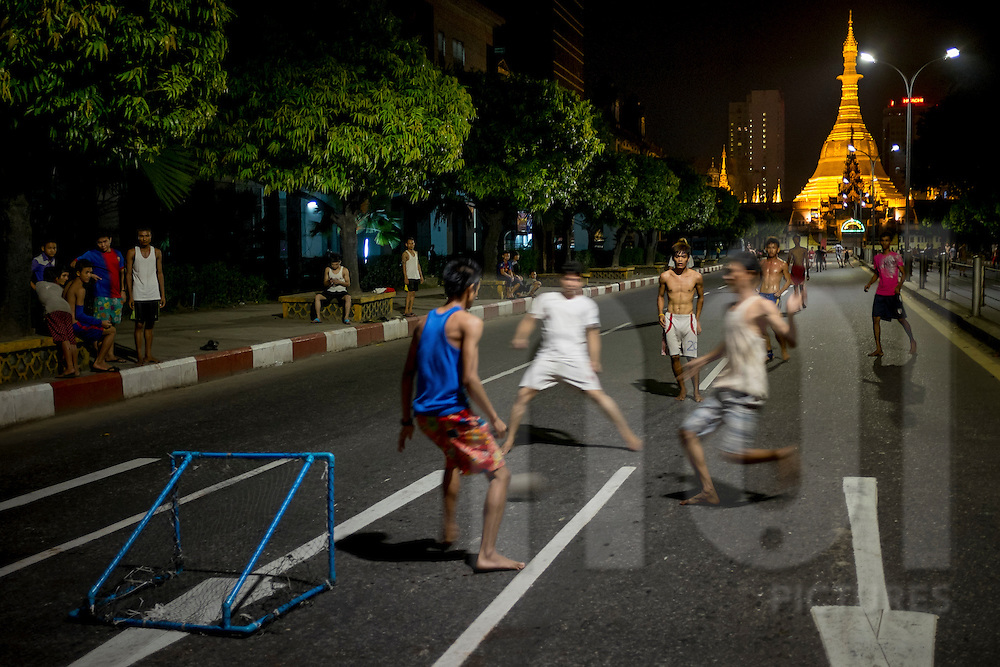 Young men play football in the middle of the street at midnight near Sule Pagoda, Yangon, Myanmar, Southeast Asia