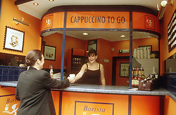 Woman buying cup of coffee from street kiosk in city centre,