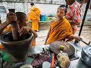 18 SEPTEMBER 2015 - BANGKOK, THAILAND:  Buddhist novices from a nearby temple in the neighborhood near Wat Kalayanamit at a som tam stand. Fiftyfour homes around Wat Kalayanamit, a historic Buddhist temple on the Chao Phraya River in the Thonburi section of Bangkok are being razed and the residents evicted to make way for new development at the temple. The abbot of the temple said he was evicting the residents, who have lived on the temple grounds for generations, because their homes are unsafe and because he wants to improve the temple grounds. The evictions are a part of a Bangkok trend, especially along the Chao Phraya River and BTS light rail lines. Low income people are being evicted from their long time homes to make way for urban renewal.             PHOTO BY JACK KURTZ