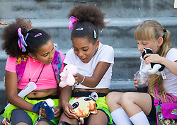 London, August 27 2017. Three girls play with their toys as they sit on the steps of a house on Ladbroke Grove as Family Day of the Notting Hill Carnival gets underway. The Notting Hill Carnival is Europe's biggest street party held over two days of the bank holiday weekend, attracting over a million people. © Paul Davey.