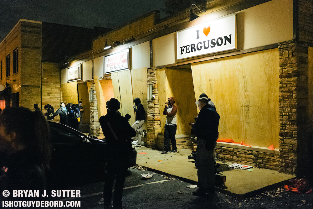 Media and onlookers stand outside boarded up businesses near the Ferguson PD after tear gas and riot cops cleared the scene on November 24th, 2014.