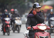 Woman talks on mobile phone while driving motorcycle in Hanoi, Vietnam on Jan 10, 2013..(Photo by Kuni Takahashi)