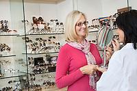 Happy senior customer looking into mirror in store