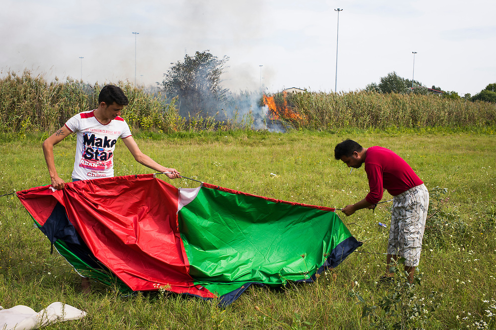 Migrants pack up their tent as brush adjacent to the border fence burns in the background on September 17th, 2015 in Horgos, Serbia. Police questioned nearby refugees about who started the fire, simultaneously, migrants blamed police for starting the fire to make it easier to monitor the border.