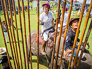 """28 AUGUST 2014 - BANGKOK, THAILAND:     A mahout and polo player selects a polo mallet for the player at the King's Cup Elephant Polo Tournament at VR Sports Club in Samut Prakan on the outskirts of Bangkok, Thailand. The tournament's primary sponsor in Anantara Resorts. This is the 13th year for the King's Cup Elephant Polo Tournament. The sport of elephant polo started in Nepal in 1982. Proceeds from the King's Cup tournament goes to help rehabilitate elephants rescued from abuse. Each team has three players and three elephants. Matches take place on a pitch (field) 80 meters by 48 meters using standard polo balls. The game is divided into two 7 minute """"chukkas"""" or halves.  PHOTO BY JACK KURTZ"""