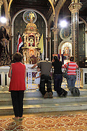 Praying at the altar of La Basilica church; Cartago, Costa Rica.<br />