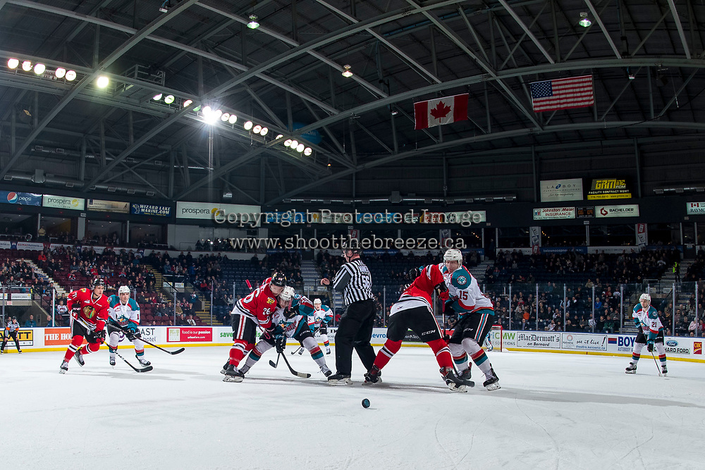 KELOWNA, CANADA - MARCH 3:  Linesman Cody Wanner stands on the ice after the face off between Mason Mannek #26 of the Portland Winterhawks and Kyle Crosbie #25 of the Kelowna Rockets on March 3, 2019 at Prospera Place in Kelowna, British Columbia, Canada.  (Photo by Marissa Baecker/Shoot the Breeze)
