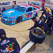 Pit crew members of Denny Hamlin (11) and Joe Gibbs Racing removes a set of tires from the race car in the course of a pit stop during the NASCAR SPRINT CUP SERIES FEDEX 400 BENEFITING AUTISM auto race at Dover International Speedway in Dover, DE., Sunday, June 02, 2013.