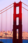 Close-up architectural detail of the Golden Gate Bridge with the city in the background, San Francisco, California. The Golden Gate Bridge is a suspension bridge spanning the Golden Gate, the opening of the San Francisco Bay onto the Pacific Ocean. As part of both US Highway 101 and State Route 1, it connects the city of San Francisco on the northern tip of the San Francisco Peninsula to Marin County. The Golden Gate Bridge had the longest suspension bridge span in the world when it was completed in 1937 and has become an internationally recognized symbol of San Francisco and the United States..Subject photograph(s) are copyright Edward McCain. All rights are reserved except those specifically granted by Edward McCain in writing prior to publication...McCain Photography.211 S 4th Avenue.Tucson, AZ 85701-2103.(520) 623-1998.mobile: (520) 990-0999.fax: (520) 623-1190.http://www.mccainphoto.com.edward@mccainphoto.com.