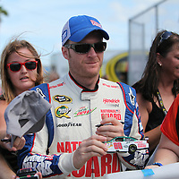 NASCAR Sprint Cup driver Dale Earnhardt Jr. (88)  sign autographs in the garage area during the NASCAR Coke Zero 400 Sprint practice session at the Daytona International Speedway on Thursday, July 4, 2013 in Daytona Beach, Florida.  (AP Photo/Alex Menendez)