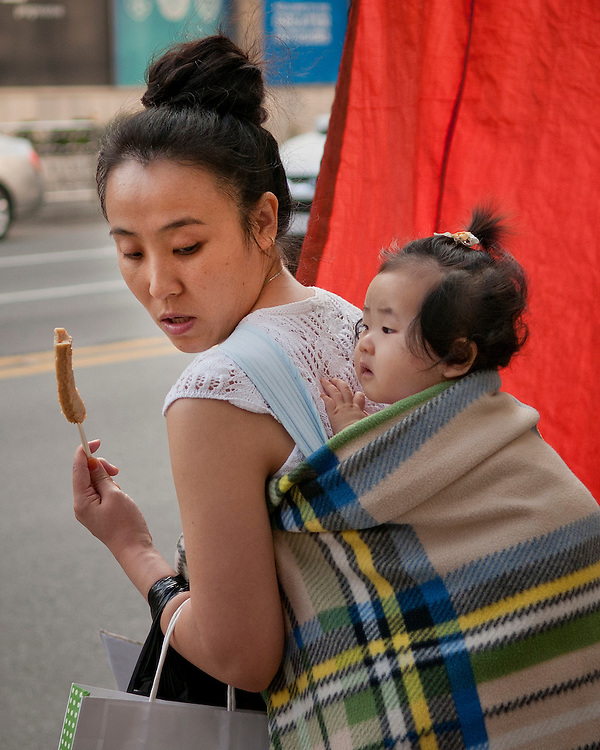 A mother offers a snack to her child while shopping in Busan, South Korea. June 3, 2011.