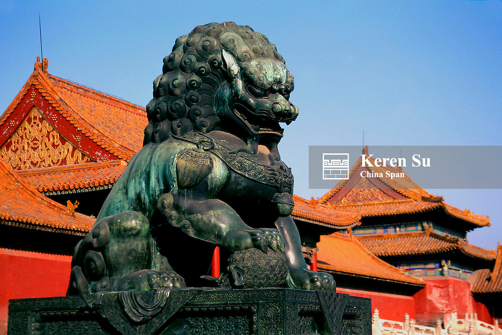 Bronze lion statue with traditional buildings at Forbidden City, Beijing, China
