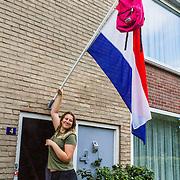 NLD/Huizen/20160619 - Hongeren geslaagd na hun schoolexamen hangen de vlag uit met hun schooltas,